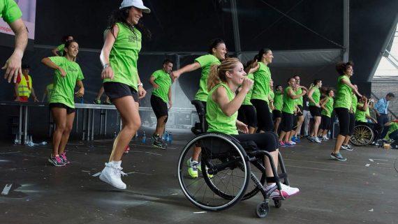 Diferents persones en un escenari dirigint les activitats de fitnes, entre ells, una noia amb cadira de rodes