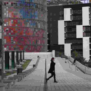 Fotografia de l'exposició de l'Arxiu Fotogràfic de Barcelona : Darius Koehli. Inside Poblenou. Es veuen edificis moderns de la Pl. de les Glòries i un noi sol que passeja entre els edificis.