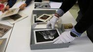 Es veu una persona amb guant manipulant fotos del fons de l'Arxiu Fotogràfic