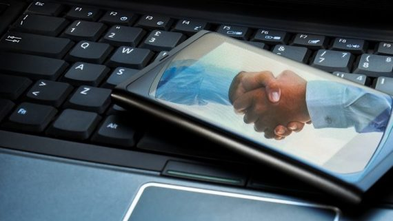 Handshake reflected on a smartphone placed on a laptop.