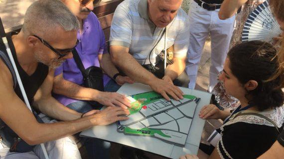 Un grup de persones amb discapacitat visual toquen un planell durant la visita a les Masies de Nou Barris