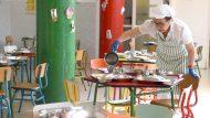 Una mujer srive comida y agua en unas zafatas. Se encuentra en un comedor escolar infantil.un menjador escolar infantil.