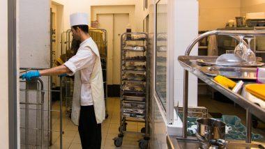 Persona treballant en una cuina, recollint safates