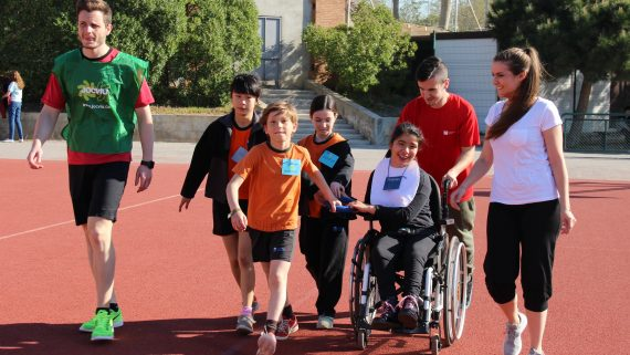 Grupo de niños y niñas corriendo en una pista de atletismo con una niña en silla de ruedas