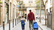 Pare amb carret de la compra i nen a un carrer de Ciutat Vella.
