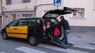 Una persona baixa d'un taxi adaptat amb cadira de rodes