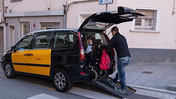 Una persona puja a un taxi en cadira de rodes