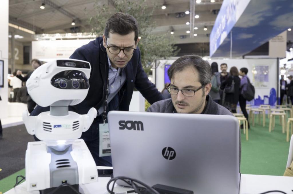 Dues persones, treballen en un portàtil per prorgamar un robot.