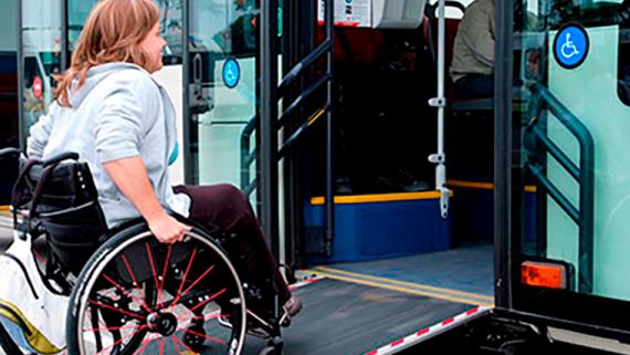 Una persona pujant al transport pública amb cadira de rodes