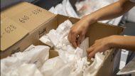 Una persones ordenant material dins de capses de cartró
