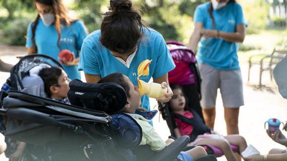 Una monitora ajuda a beure aigua a un infant en cadira de rodes en el marc de les activitats de lleure inclusiu de l'estiu 2020