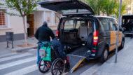 Taxi adaptat per a persones amb mobilitat reduïda amb un home en cadira de rodes entrant al seu interior.