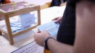 Una persona está delante de la urna de votación con la papeleta en la mano