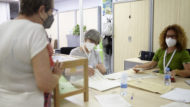 Dos responsables revisan si la persona que va a votar está inscrita en el censo electoral