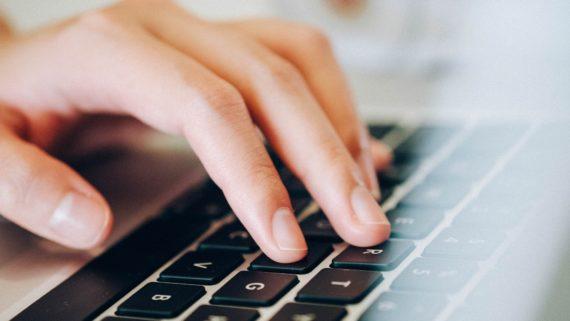 Mans teclejant en un ordinador.