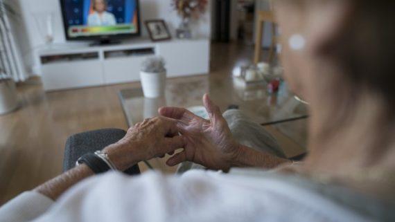 Una dona gran mirant la televisió a casa seva.