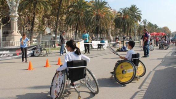 Nens i nenes amb cadira de rodes jugant en equip.